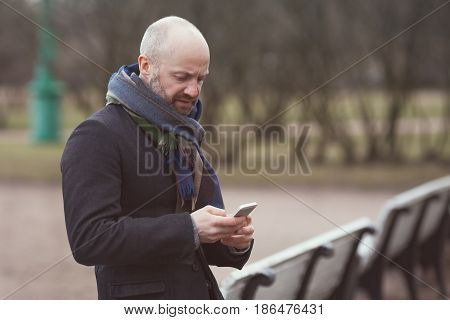 A Man Is Standing In The Street And Waiting For Someone. He Looks At His Phone And Dials A Number.