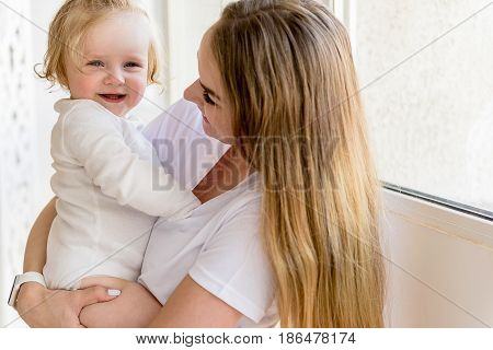Happy young mother is playing with her little daughter while holding the infant. She is standing and looking at baby with admiration. Girl is laughing