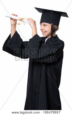 Portrait of a graduate little girl student in a black graduation gown with hat, holding diploma - isolated on white background. Child back to school and educational concept.