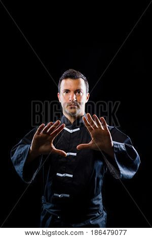 Man exercise Tai Chi over black background
