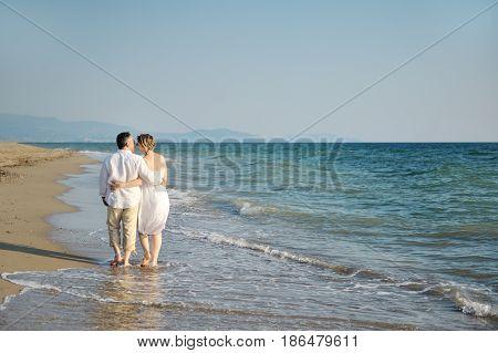 Happy romantic couple embraced walking on the beach near sea