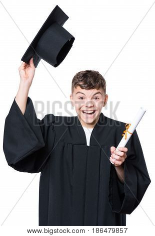 Portrait of a happy graduate teen boy student in a black graduation gown with hat and diploma - isolated on white background. Lucky cheerful schoolboy celebrating triumph.