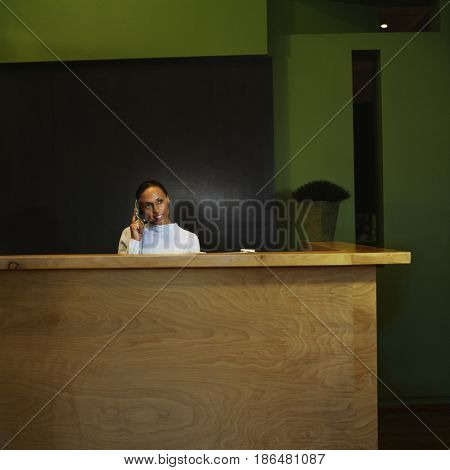 Woman working at reception desk in office