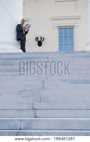 Caucasian businessman leaning against pillar reading newspaper