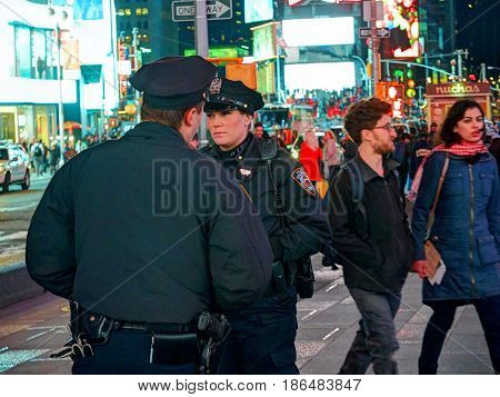 NEW YORK TIMES SQUARE, APR,24, 2015: Most beautiful New York Times Square police officer woman among tourists and people. NYC NYPD pretty police girl woman. Big apple cop Times Square police officers
