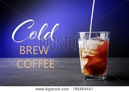 Pouring milk into glass with cold brewed coffee on color background
