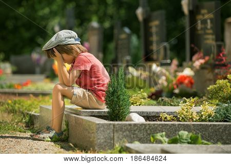 Sad Little Boy, Sitting On A Grave In A Cemetery, Feeling Sad