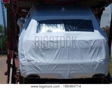 Dallas,USA,14May2017. A clean car transport prepares a shipment of new autos with zip cover bags to protect the finishes.