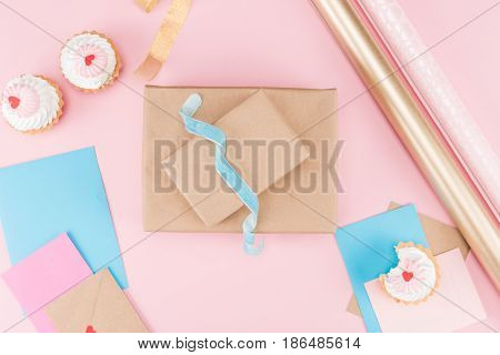 Top View Of Delicious Cupcakes, Blank Cards, Ribbon, Wrapping Paper And Unpacked Gift Box On Pink, B