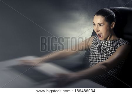 Business woman playing computer games on a dark background.