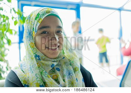 happy muslim girl sitting waiting for her flight