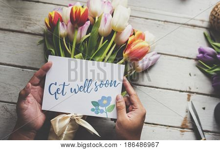 Hand Holding Show Get Well Soon Card with Tulips Flowers Background