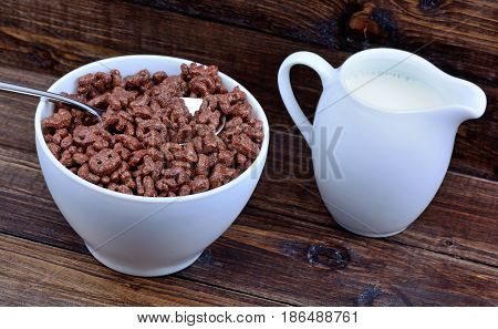 Cocoa cereals in a bowl with milk on wooden table