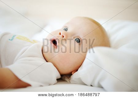 Portrait of a young child in white clothes against the background of a baby crib