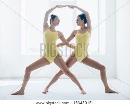 Two Young Women Doing Yoga Asana Warrior Pose Variation