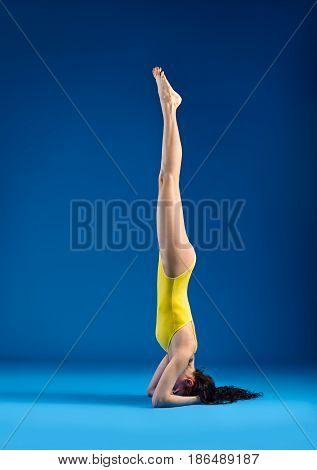 Young woman doing yoga asana supported headstand Salamba Sirsasana. side view