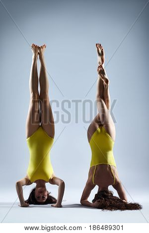 Two Young Women Doing Yoga Asana Supported Headstand