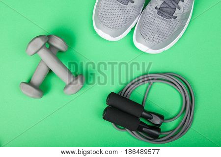 Sport shoes dumbbells and skipping rope on green background. Top view. Fitness sport and healthy lifestyle concept.