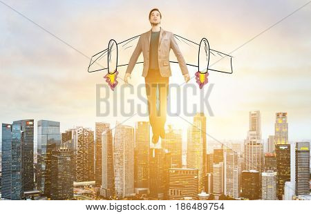 Business Advantage. Businessman with sketch wings hovering over down town on sunset.