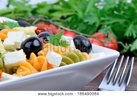 Colorful fusilli with vegetable in a plate on wooden table