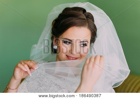 Beautiful young shy bride hiding her face behind veil.