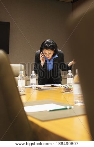 Mixed race businesswoman working in empty conference room