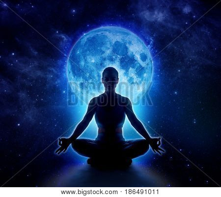 Yoga woman in full blue moon and star. Meditation girl sitting in lotus pose under moonlight in dark night sky Moon original image from NASA.gov