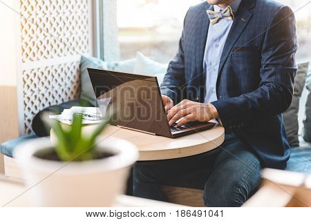 Man working on laptop while sitting at table in comfortable office