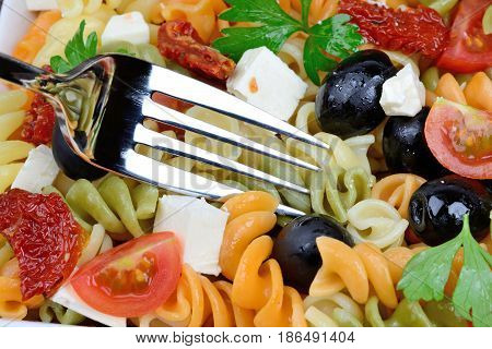 Colorful pasta with olive cheese and tomato close-up