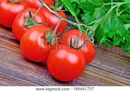Tomatoes with parsley on wooden table closeup