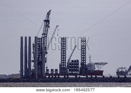 Offshore wind farm construction. Investment in renewable clean energy as a supply vessel ship is docked and ready to receive wind turbine parts.