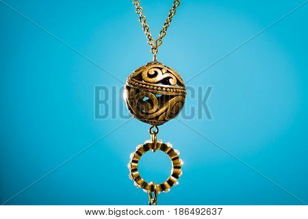 Cheap metal pendant necklace from bazaar on blue background.