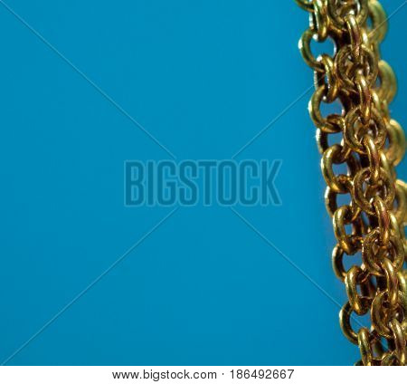 Gold chain on blue background right side of the photo.