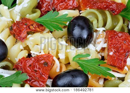 Colorful pasta with olive dried tomatoes cheese and parsley close-up