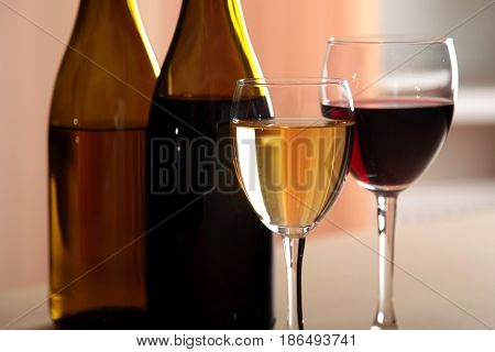 A glass of white wine and a glass of red wine next to bottles of white wine and red wine