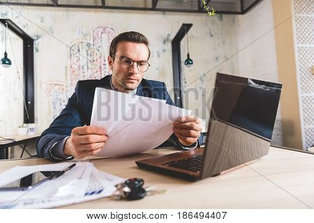 Serene bristled businessman watching at paper while working in comfortable office
