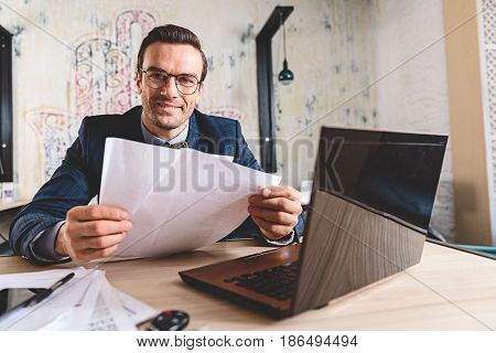 cheerful intelligent bristled male looking at papers while sitting at table in cozy apartment