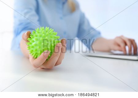 Woman holding rubber ball at work space