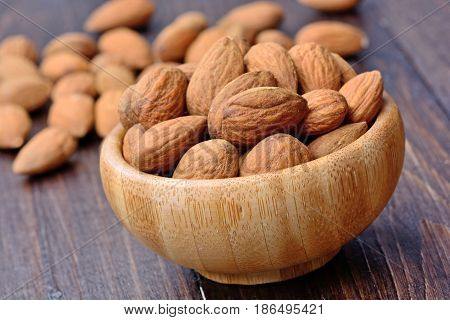 Almonds in a bamboo bowl on wooden table