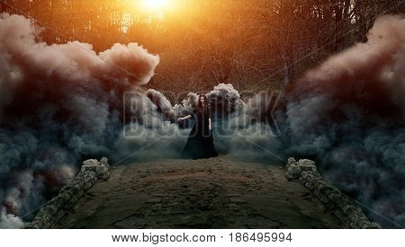 Young attractive Witch in black dress walking on the old bridge in heavy black smoke. Dark magic. Horror fairy tale.