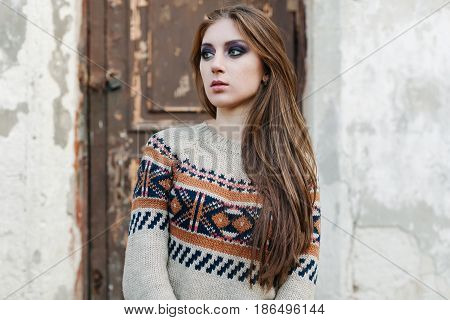 Beautiful Woman with long hair in winter pullover. Healthy hair. Grey background with vintage brown door