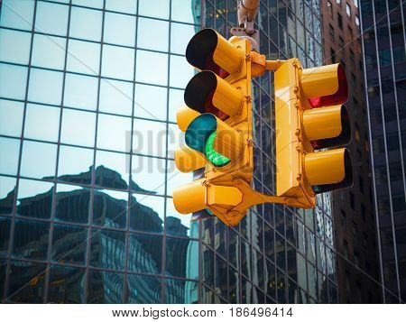 View on wall street yellow traffic light with black and white pointer guide. Green traffic light to Wall street banks money dollars finance offices. New York holidays vacations tours and architecture