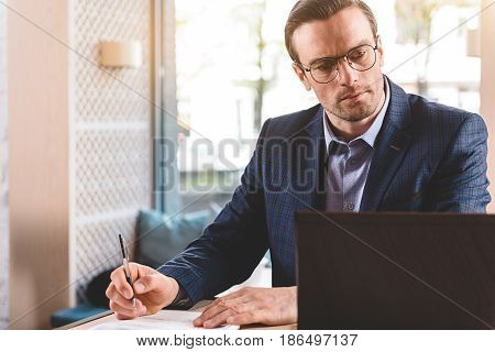 Serious bristled businessman looking at screen of notebook computer while sitting at desk in office