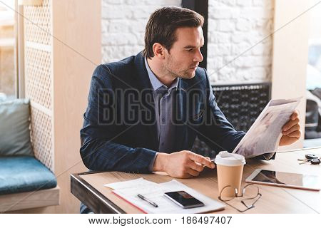 Side view serene bristled smart operator reading article while sitting at table in cozy cafe