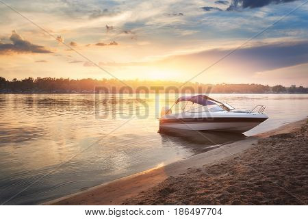 Colorful sunset with boat ot the river bank. Summer landscape with pleasure boat river bright sky with clouds and yellow sunlight reflected in water trees and beach. Amazing view on the lake