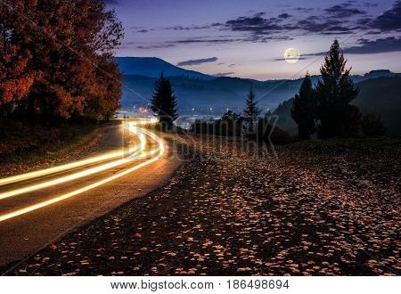 countryside road with car lights. beautiful autumn mountain landscape at night in full moon light