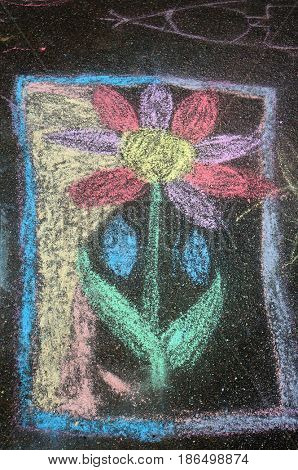 Child's crayon drawing of flower on asphalt foot pavement.