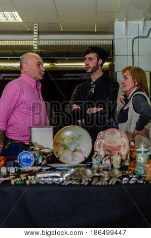 Moscow, Russia - March 19, 2017: Group of three antiques dealers discuss the deal at meeting at the fair of antique hobby and collectors items. Business success concept