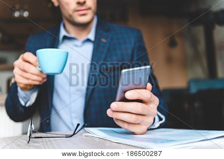 Serene bristled male looking at mobile phone while tasting mug of hot beverage in confectionary shop