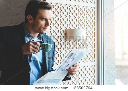 Serene bristled male tasting cup of appetizing coffee while reading newspaper. He standing near window